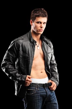 Vertical shot of a handsome shirtless guy on black background