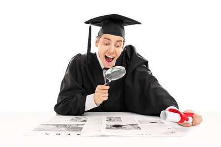 College graduate searching for job in newspaper isolated on white background