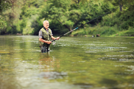 Mature fisherman fishing in a river with a fishing rodの写真素材
