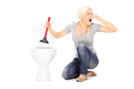 Woman unclogs a stinky toilet with plunger isolated on white background