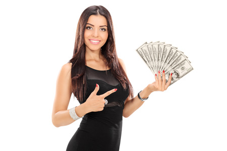 Woman pointing towards a stack of money with her finger isolated on white background
