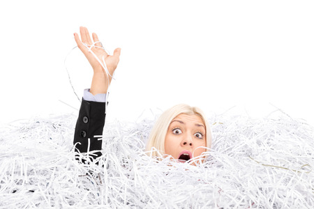 Businesswoman drowning in a pile of shredded paper isolated on white background