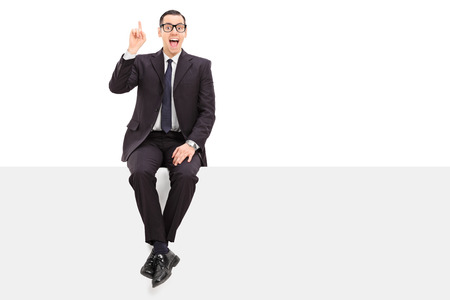 Young businessman has an idea seated on a panel isolated on white background