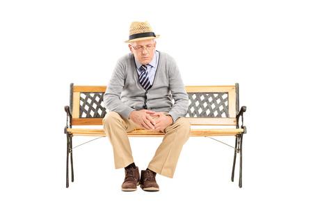 Sad senior thinking seated on a bench isolated on white background