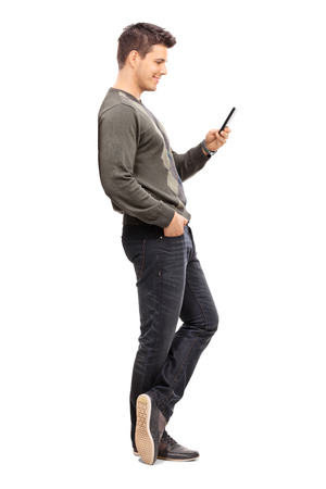 Photo pour Full length portrait of a young man texting on his cell phone isolated on white background - image libre de droit