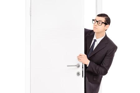 Businessman peeking through an opened door isolated on white background
