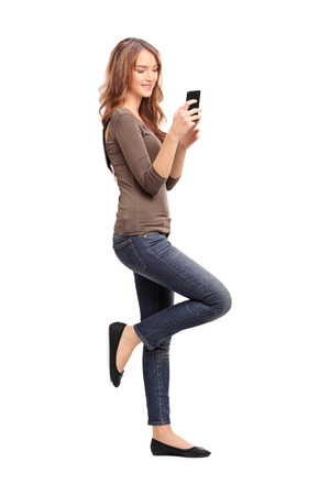 Photo pour Full length portrait of a young woman typing a text message on her cell phone and leaning against a wall isolated on white background, studio shot - image libre de droit