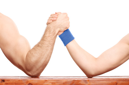 Close-up on an uneven arm wrestling contest between a muscular arm and a skinny one isolated on white background