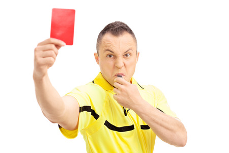 Furious football referee showing a red card and blowing a whistle isolated on white background