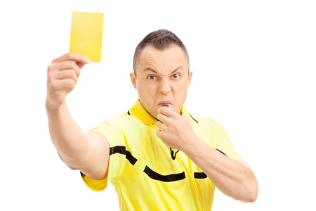 Furious football referee showing a yellow card and blowing a whistle isolated on white background