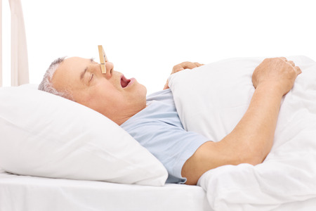 Senior sleeping in a bed and snoring with a clothespin stuck on his nose isolated on white background