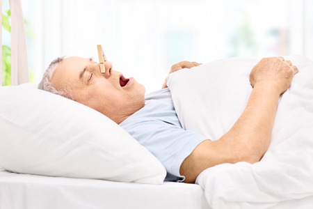 Senior man sleeping with a clothespin on his nose and snoring at home