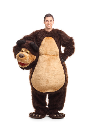 Full length portrait of a young man in a bear costume smiling and looking at the camera isolated on white background