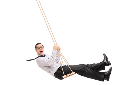 Delighted young man swinging on a swing and looking at the camera isolated on white background