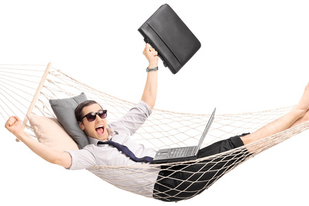 Young businessman lying in a hammock with a laptop in his lap and gesturing joy isolated on white