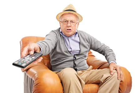 Photo pour Angry senior man pressing buttons on a remote control seated in an armchair isolated on white background - image libre de droit