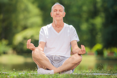 Peaceful senior man meditating seated on a blanket in a park by a lake