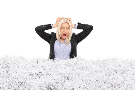 Studio shot of a young furious businesswoman stuck in a pile of shredded paper isolated on white background