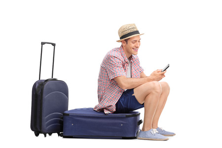 Young male tourist typing a text message on his cell phone an sitting on his luggage isolated on white background
