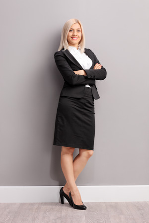 Full length portrait of a young businesswoman in black suit leaning against a gray wall and looking at the camera