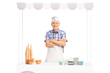 Mature ice cream vendor standing behind a kiosk and looking at the camera isolated on white backgroundの写真素材