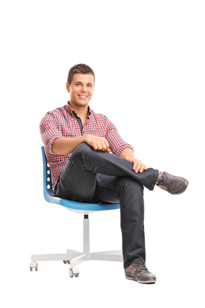 Vertical studio shot of a relaxed young man sitting on a chair and looking at the camera isolated on white background