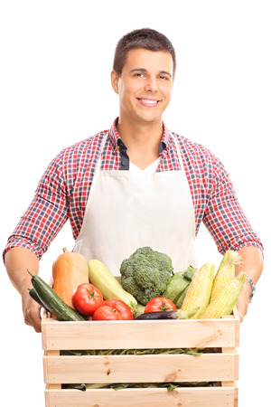Vertical shot of a young man with a white apron holding a wooden crate full of fresh vegetables and looking at the camera isolated on white background