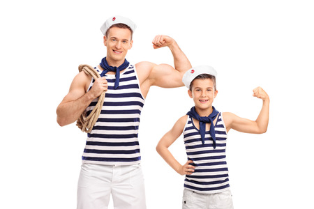 Young man and a child in sailor uniforms showing biceps and looking at the camera isolated on white background