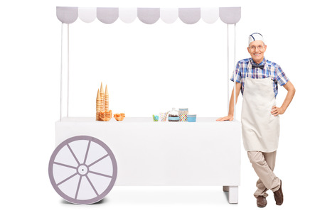 Cheerful senior ice cream vendor posing next to a stall with waffle cones and other candy on it isolated on white background
