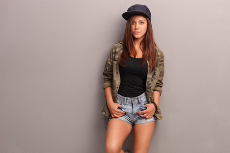 Cool teenage girl in trendy clothes leaning against a gray wall and looking at the camera