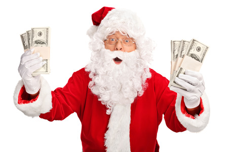 Santa Claus holding few stacks of money and looking at the camera isolated on white background