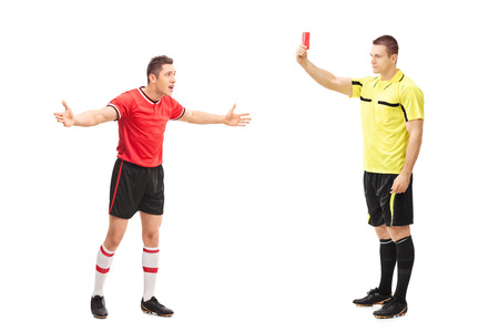 Full length portrait of a football referee showing a red card to an angry player isolated on white background