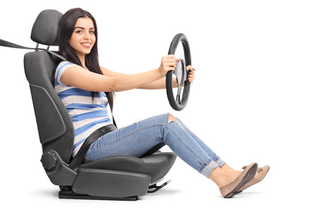 Young cheerful woman pretending to drive seated on a car seat isolated on white background