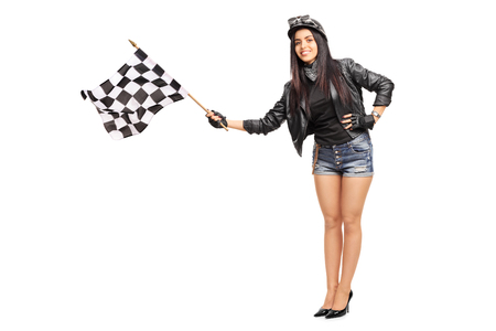 Photo pour Full length portrait of a young female biker waving a checkered race flag isolated on white background - image libre de droit