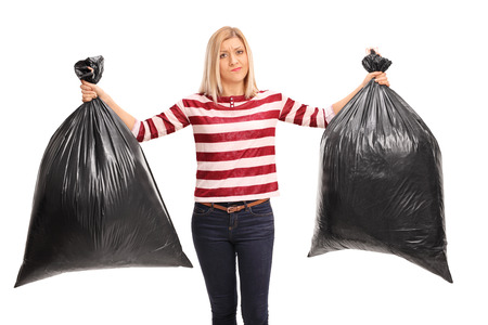 Displeased young woman holding two black trash bags and looking at the camera isolated on white background