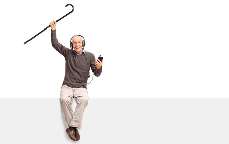 Senior man listening to music on headphones and lifting his cane in the air seated on a blank panel isolated on white background