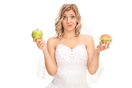 Photo for Young bride holding an apple in one hand and a hamburger in the other isolated on white background - Royalty Free Image