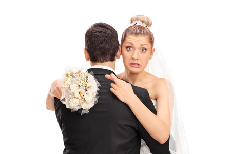 Foto de Young blond bride hugging her husband with her fingers crossed isolated on white background - Imagen libre de derechos