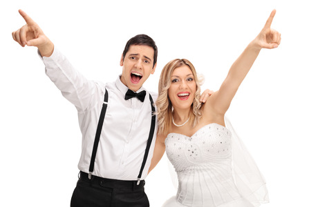 Photo pour Joyful bride and groom singing together and pointing up with their hands isolated on white background - image libre de droit