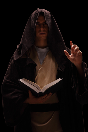 Vertical shot of a mysterious monk holding a book and preaching on black background