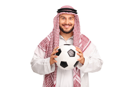 Studio shot of a young Arab holding a football and looking at the camera isolated on white background