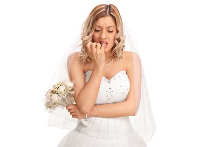 Foto de Young nervous bride in a white wedding dress biting her fingernails isolated on white background - Imagen libre de derechos