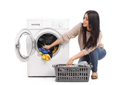 Photo pour Young woman emptying a washing machine isolated on white background - image libre de droit