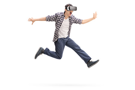 Photo pour Excited young man experiencing virtual reality through a VR headset shot in mid-air isolated on white background - image libre de droit