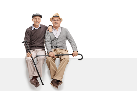 Foto de Two senior pals holding canes and sitting on a blank white signboard isolated on white background - Imagen libre de derechos