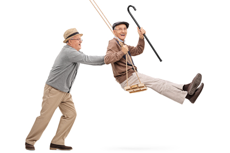 Two joyful senior gentlemen swinging on a swing and having fun isolated on white background
