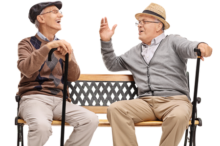 Two retired elderly people sitting on a bench and laughing isolated on white background