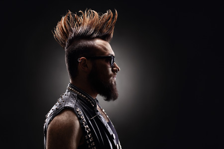 Photo pour Profile shot of a young punk rocker with a Mohawk hairstyle on dark background - image libre de droit