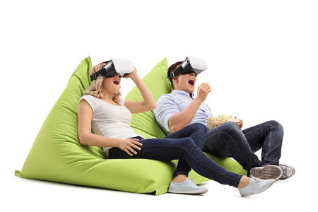 Photo pour Excited young couple experiencing virtual reality seated on beanbags isolated on white background - image libre de droit