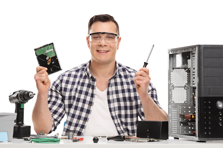 Male PC technician holding a computer part and a screwdriver isolated on white background